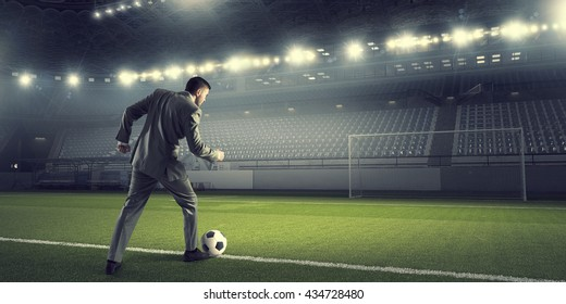 Businessman kicking ball