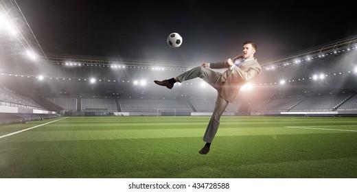 Businessman kicking ball