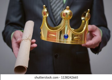 Businessman king holding in hands a gold crown and royal decree scroll (special offer document).