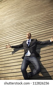 businessman knocked down on a wooden floor. young man on wooden floor with open arms