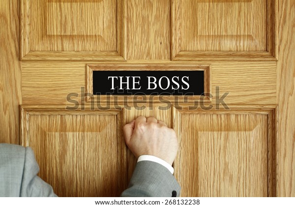 "Businessman knocking on a door to ""The Boss"" office concept for meeting, trouble, problems, promotion or being fired"