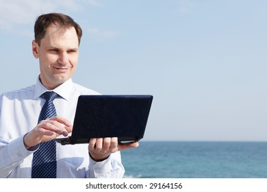 Businessman with laptop against sea background