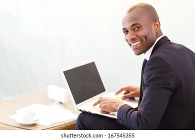 Businessman with laptop. Cheerful young African businessman typing something on laptop and looking over shoulder