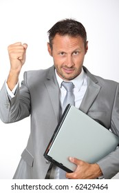 Businessman with laptop computer lifting arm up
