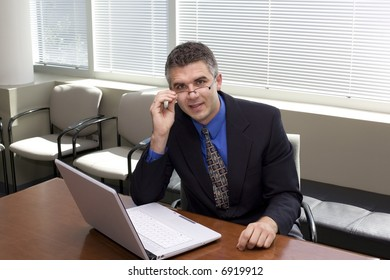 A businessman with a laptop in a conference room