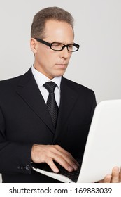 Businessman with laptop. Confident mature man in formalwear working on laptop while standing against grey background