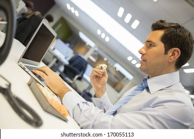 Businessman with laptop eating sushi at his desk.