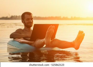 Businessman with a laptop on inflatable ring in the water at sunset