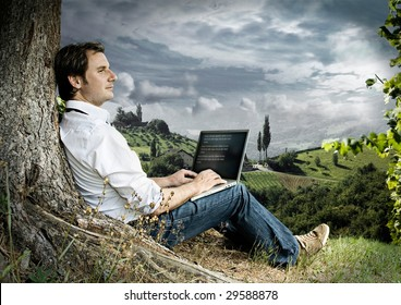 businessman with laptop on a meadow with dark clouds