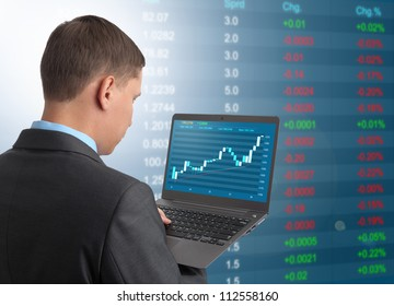 Businessman with laptop on Stock Market Background