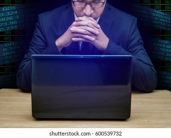 a businessman and laptop on wooden table and stock data graphic