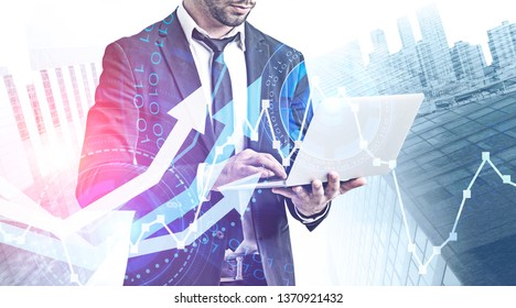 Businessman with laptop over abstract city background with growing graphs and HUD interface. Stock market analysis concept. Toned image double exposure