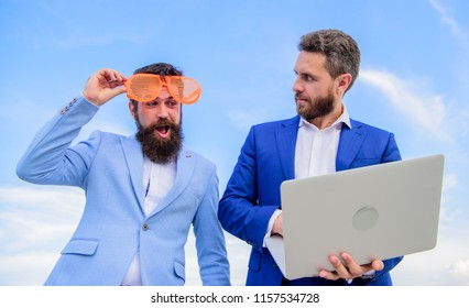 Businessman with laptop serious while business partner ridiculous glasses looks funny. How stop play entrepreneurship and get serious business. Event management industry. Unprofessional behaviour.