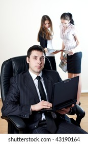 businessman with laptop sit in an armchair with collgues on backside