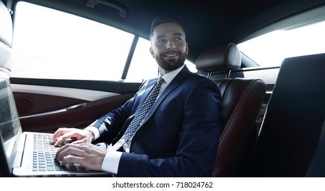 businessman with laptop sitting in the back seat of a car