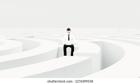 businessman with laptop sitting on the middle of labyrinth
