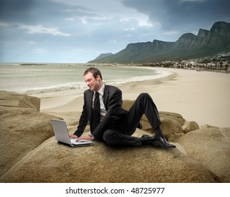 Businessman with laptop sitting on a rock looking over a seascape
