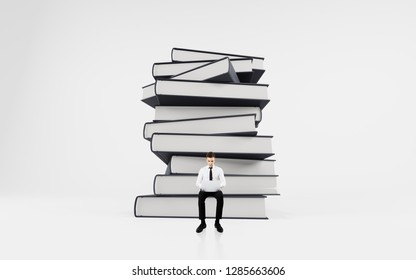 businessman with laptop sitting on a stack of books. Education concept