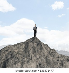 businessman with laptop standing on mountain
