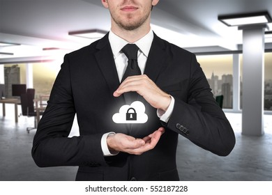 businessman in large office protecting cloud security with hands