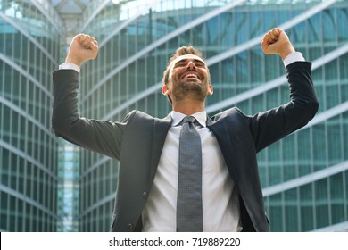 A businessman laughed with open arms and smiling for her success in working in the economic and financial sphere. Concept of: success, exultation, business, freedom.