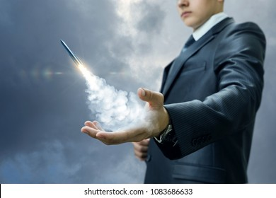 Businessman launches a missile from the hand on sky background. Concept of start up.