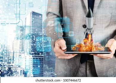 Businessman launches rocket from a tablet. concept of company startup