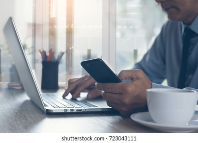 Businessman, lawyer in blue shirt and necktie holding mobile smart phone and concentrate working on laptop computer with cup of coffee on desk in office, close up, business and financial concept