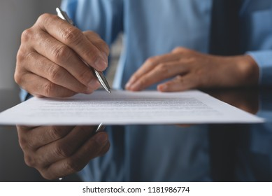 Businessman, lawyer in blue shirt signing official contract. Man with pen in hand writing paper on mirror desk with copy space and reflection, close up. Business agreement concept