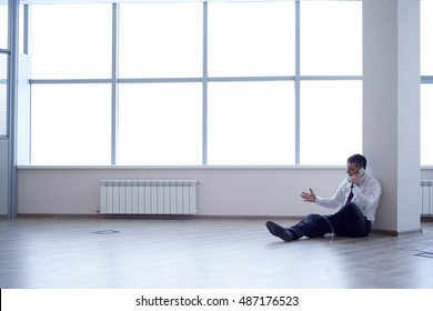 Businessman (lawyer, insurance agent, supervisor, manager) is sitting on the floor in an empty office. Next to him, only the phone/Business Went Bankrupt