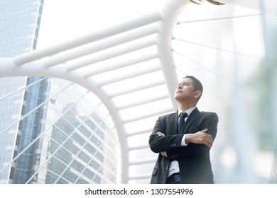 businessman or a lawyer stands firmly in his arms. With an office view as a backdrop, positive concepts Confidence and faith are the means of success.
