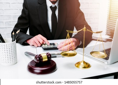 Businessman or lawyer working on accounts using a calculator and laptop computer and documents in office.justice and law concept.