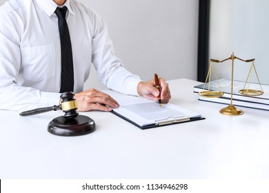 Businessman or lawyer working on a documents, judge gavel with Justice lawyers at law firm in background, Legal law, advice and justice concept.