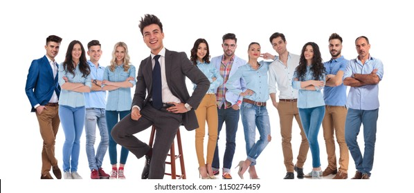 businessman leader of casual team sitting on chair in front of them on white background, looking up to side