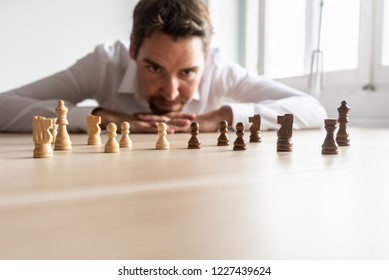Businessman leaning his head on his palms on office desk looking at white against black chess pieces arranged on wooden desk with copy space.