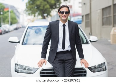 Businessman leaning on the bonnet of his car