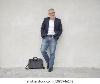 Businessman leaning on concrete wall, full length