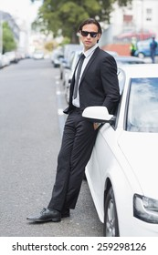 Businessman leaning on the door of his car