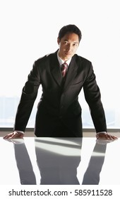 Businessman leaning on table, looking at camera