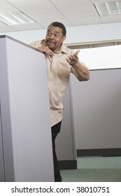Businessman leaning over a cubicle to talk his neighbor.