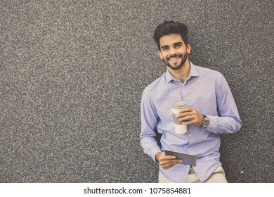 Businessman leaning to wall using iPod and having pause drinking coffee.