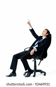 Businessman leans back on his office chair and points up into the air, trying to visualize something