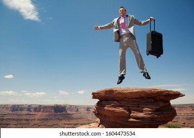 Businessman leaping with a wheelie carry-on case looking out over massive red rock canyon landscape