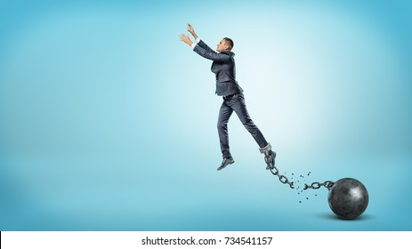 A businessman leaps up with outstretched hands while he's chained to an iron ball with a broken link. Breaking boundaries. Reach your goal. Business restrictions.