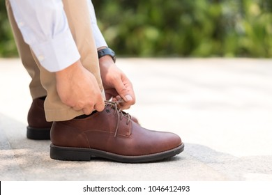 Businessman with leather shoes tying shoe laces, get ready to work or go outside