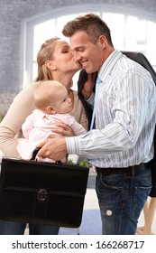 Businessman leaving for work, wife and baby daughter saying good-bye to him.