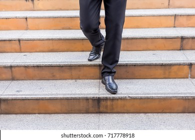 Businessman legs taking step on a lower level on a stairs - bad business investment decision concept