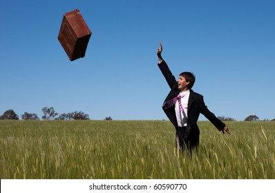 Businessman letting go and release past baggage and instantly enjoys the freedom against a blue sky green grass landscape.
