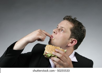 Businessman licking his fingers while eating a hamburger for lunch