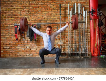 businessman lifting barbell against a brick wall in the gym